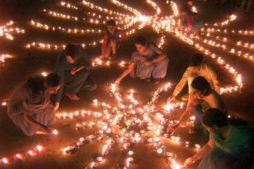179728-indian-women-light-lamps-on-eve-of-diwali-the-hindu-festival-of-lights